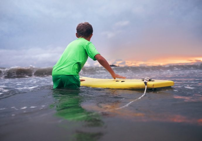Boy learning to surf in ocean waves at sunset time